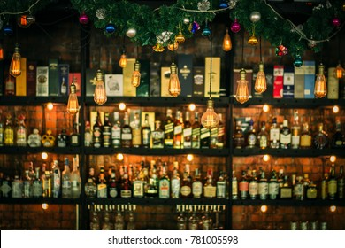 Liquor bar and many alcohol drinks behind the bar with vintage lamps