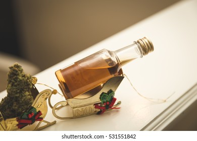 Liquor bottle and cannibus in gold sleigh ornaments.