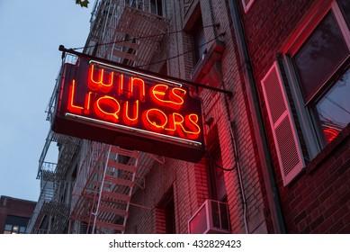 Liquor store neon sign on brick building background