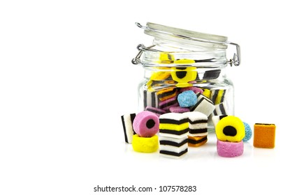 Liquorice allsort sweets in storage jar isolated over white background.