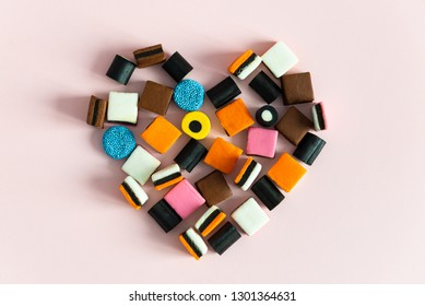 Liquorice Allsorts Sweets in heart shape on pink background.