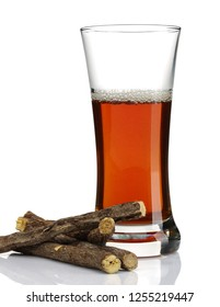 Liquorice root and a glass of tea isolated on white background