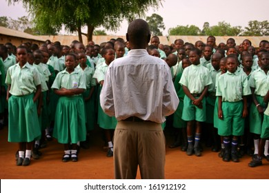 LIRA, UGANDA - FEBRUARY 27, 2012 - A teacher stand in front of his class as they open the day by singing the Ugandan national anthem.