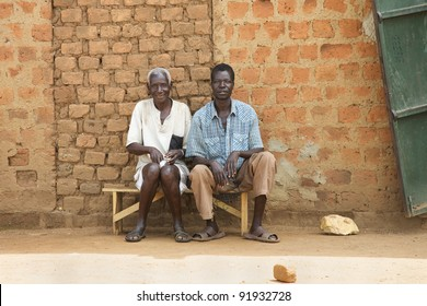 LIRA, UGANDA - JUNE 9: Two villagers wait on bus bench in Lira, Uganda on June 9, 2007. The median age in Uganda is very young at 15.1 years and population growth is only 3.576%