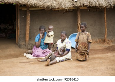 LIRA, UGANDA - JUNE 9: An unidentified family sits on the dirt ground outside their thatched roof hut in Lira, Uganda on June 9, 2007. UNHCR estimates there to be over 136,000 refugees in Uganda.