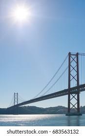 Lisbon 25 april suspension bridge against blue sky and sun, Portugal