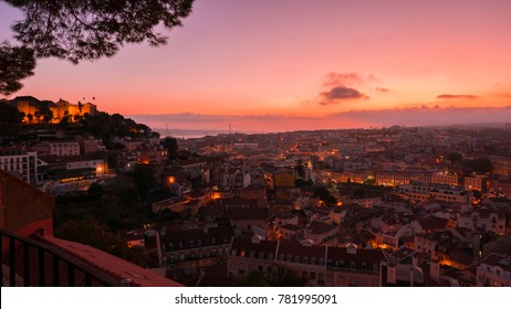 LISBON, circa 2017 - Wide angle aerial shot of Lisbon, Portugal at dusk overseeing the Castelo de Sao Jorge castle, the downtown, the Tagus river, the Cristo Rei and the Ponte 25 de Abril bridge