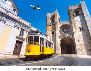 Lisbon city old town and famous yellow tram 28 in front of Santa Maria cathedral on a sunny summer day. Trams in Lisbon, Portugal. Tourist attraction