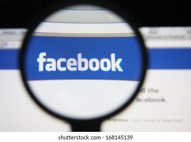 LISBON - DECEMBER 20, 2013: Photo of Facebook homepage on a monitor screen through a magnifying glass.