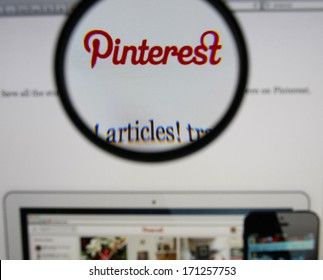 LISBON - JANUARY 14, 2014: Photo of Pinterest homepage on a monitor screen through a magnifying glass.