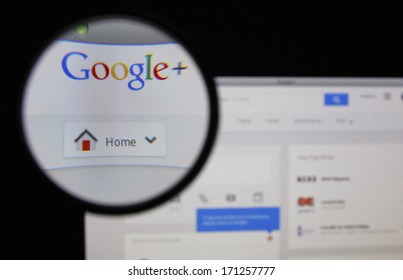 LISBON - JANUARY 14, 2014: Photo of Google+ homepage on a monitor screen through a magnifying glass.