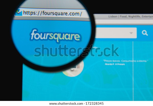 LISBON - JANUARY 20, 2014: Photo of Foursquare homepage on a monitor screen through a magnifying glass.