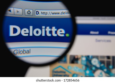 LISBON - JANUARY 23, 2014: Photo of Deloitte homepage on a monitor screen through a magnifying glass.