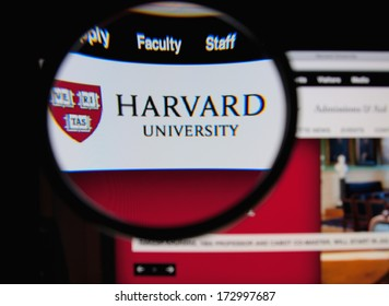 LISBON - JANUARY 25, 2014: Photo of Harvard University homepage on a monitor screen through a magnifying glass.