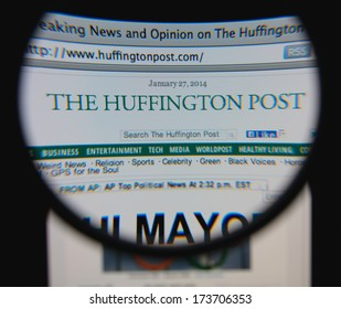 LISBON - JANUARY 29, 2014: Photo of The Huffington Post homepage on a monitor screen through a magnifying glass.
