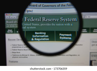LISBON - JANUARY 29, 2014: Photo of Board of Governors of the Federal Reserve System homepage on a monitor screen through a magnifying glass.