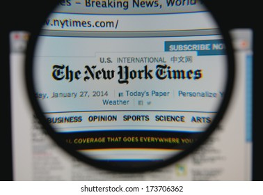 LISBON - JANUARY 29, 2014: Photo of the The New York Times homepage on a monitor screen through a magnifying glass.