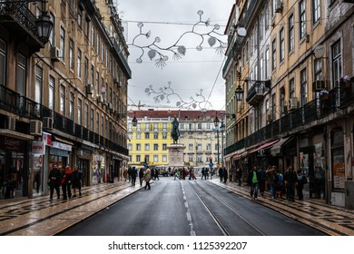 LISBON - JANUARY 3, 2018: Street leading to the Equestrian statue of King John I in the Praça da Figueira square in Lisbon, Portugal, busy with locals and tourists on a rainy Winter morning.