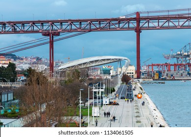 LISBON - JANUARY 4, 2018: Aerial view of people walking along the promenade by the river Tagus leading to the Santa Amaro dock at the base of the 25 de Abril bridge in Lisbon.
