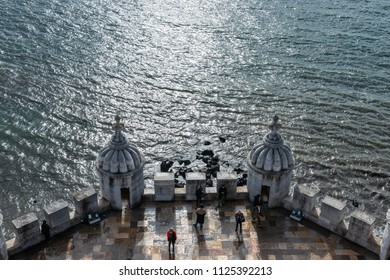 LISBON - JANUARY 4, 2018:Elevated view of tourists enjoying the view from the Torre de Belém (built 16th century) by the Tagus River in Lisbon on a cloudy Winter day.