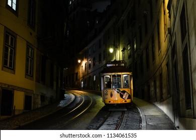 LISBON – JANUARY 4, 2018: Traditional yellow tram in a narrow street (Calcada Sao Francisco) in Lisbon on a rainy Winter night.