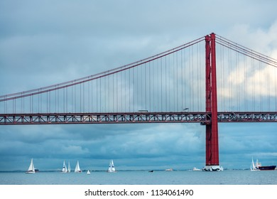 LISBON – JANUARY 4, 2018: Wide-angle view of sailboats sailing around the 25 de Abril bridge in Lisbon on a cloudy Winter afternoon.