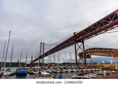 LISBON - JANUARY 4, 2018: Wide-angle view of boats moored at the Santa Amaro dock under the 25 de Abril bridge in Lisbon at dusk.