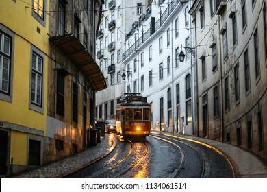 LISBON – JANUARY 5, 2018: Traditional tram and incidental cars in a narrow street (Calcada Sao Francisco) in Lisbon on a rainy Winter day.