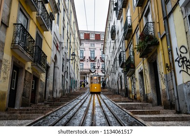 LISBON - JANUARY 5, 2018: Traditional yellow tram and incidental people in a narrow street in Lisbon on a rainy Winter day.
