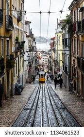 LISBON – JANUARY 5, 2018: Traditional yellow tram and incidental people in a narrow street in Lisbon on a rainy Winter day, with the river Tagus defocused in the background.