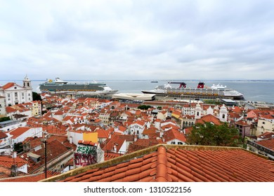 LISBON – July 25, 2018:  Spectacular view over the roof tops of Alfama old city towards the cruise terminal and the Tagus River, from Santa Luzia Belvedere in Lisbon, Portugal