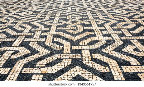 LISBON – July 3, 2018: Typical Portuguese cobblestone pavement creating balck and white patterns using basalt and limestone cobbles, in Lisbon, Portugal