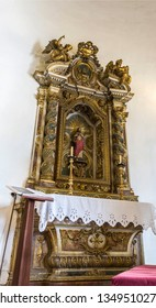LISBON – July 5, 2018: View of the gilded side altar in the Chapel of Saint Amaro with a statue of Saint Amaro peregrine, in Alcantara, Lisbon, Portugal