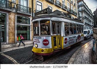 Lisbon, Portugal -05.17.2018: Historical yellow tram 28 passing  in front of the Lisbon cathedral.Vintage tram in Lisbon,