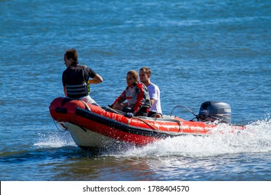 Lisbon, Portugal 07/12/2010: A young blonde woman and two young men are on an inflatable boat with outboard engine. They move fast in water. This is an isolated image showing the three in river.