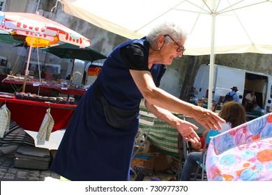 Lisbon, Portugal - 08.19.2017: an old woman setting up a sun umbrella at a junk market.