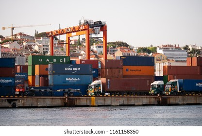 LISBON, PORTUGAL - 1 AUGUST 2018: Port of Lisboa. Cargo trucks at the Port of Lisbon on the banks of the Tagus River with a backdrop of shipping containers waiting to be transported.