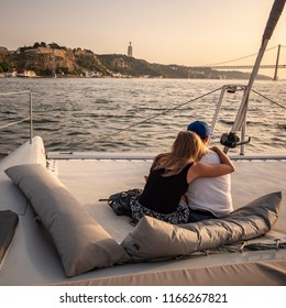 LISBON, PORTUGAL - 1 AUGUST 2018: A young couple enjoying a dusk cruise on the Tagus River with the landmarks of the Christ the King statue and and the 25 April Bridge visible in the distance.