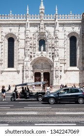 LISBON, PORTUGAL - 1 AUGUST 2018: Tourists around the south portal Manueline entrance to the Church of Santa Maria, part of the  UNESCO heritage site Jeronimos Monastery.