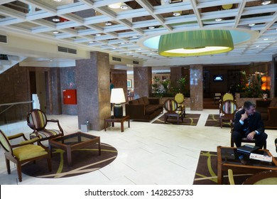 Lisbon, Portugal - 10.23.2012: softly & selectively focused elegant hotel lobby. Fenix hotel. Business man sitting at coffee table having discussion & meeting. hotel lobby interior with chairs & table