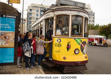 Lisbon, Portugal - 12 September, 2014: a long queue of tourists are waiting at the tram stop to board a historic route number 28 of a vintage yellow tram in the capital of Portugal