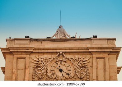 Lisbon, Portugal - 12/26/18: Huge famous Rua Augusta Arch. Triumphal historical building attraction with big enormous clock tower. Coat of arms, sculpture.