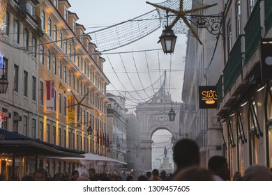 Lisbon, Portugal - 12/26/18: Huge famous Rua Augusta Arch, Christmas decorations in downtown Lisbon, Foggy Christmas evening. smoke from chestnuts
