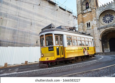 LISBON, PORTUGAL, 14, December, 2018: Wooden historicalvintage yellow street tram 28 moving near  Lisbon Cathedral, symbol of city. Indispensable transport for locals and interesting attraction
