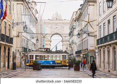LISBON, PORTUGAL, 14, December, 2018: Wooden vintage yellow street tram 28 moving near  Augusta Street, symbol of city. Indispensable transport for locals and interesting attraction for tourists