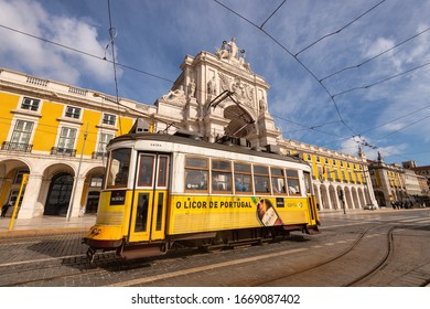Lisbon, Portugal - 2 March 2020: Famous yellow Tram 28 at the Praca do Comercio in front of Arco da Rua Augusta