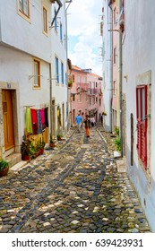 Lisbon, Portugal - 2015 04 15: People walking on a narrow street of Lisbon in Mouraria / Alfama district