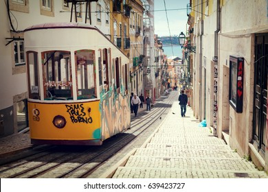Lisbon, Portugal, 2015 04 17 - yellow tram - elevador da Bica standing on top of the rails, vintage color style