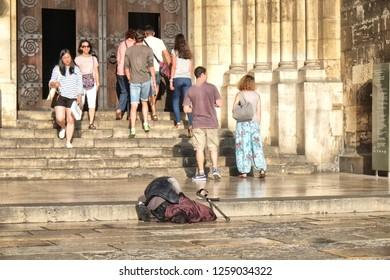 Lisbon, Portugal - 30.07.2016: Wealth meets poverty outside a church