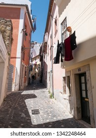 LISBON, PORTUGAL - 31 JULY 2018: A view of a typical steep and narrow alleyway in the crowded Old Town district of Lisboa, Portugal with its traditional black and white cobblestones.